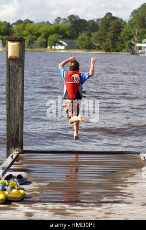 Boy in life vest  jumping off pier - Stock Photo