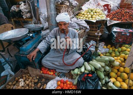 A fruit and vegetable vendor smoking a hookah, market in Luxor, Qena, Egypt. - Stock Photo