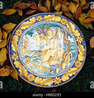 Musician with different musical instruments, with Adam and Eve being expelled from Paradise in the background, majolica - Stock Photo