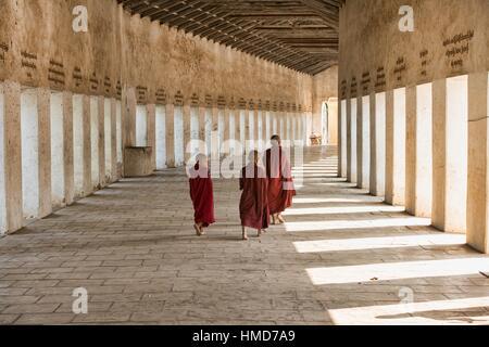 Monks walking in the entrance corridor to Shwezigon Paya, Bagan, Myanmar. - Stock Photo