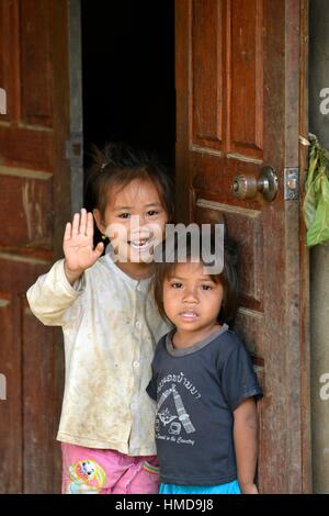Smiling little girl showing her hand up in north Laos, South East Asia. - Stock Photo