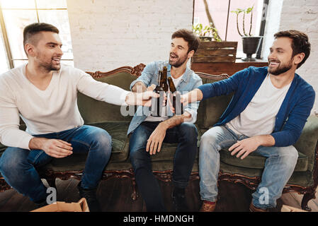 Delighted handsome man having beer - Stock Photo
