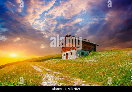 House in the mountains at sunset - Stock Photo