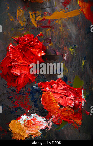 Top view of red and orange paints being mixed - Stock Photo
