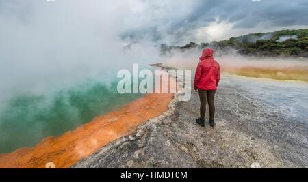Woman standing on edge of Champagne Pool, hot spring, Waiotapu Geothermal Wonderland, Rotorua, North Island, New - Stock Photo
