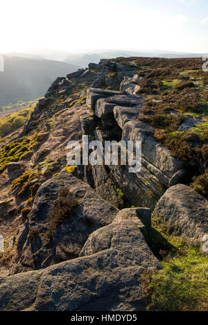Rocks on Bamford edge in the Peak District park with summer sunlight on the hillside. A rugged Derbyshire landscape. - Stock Photo