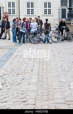 COPENHAGEN, DENMARK - SEPTEMBER 10, 2011: bicycle tourists on square in Amalienborg royal residence. Bicycling is - Stock Photo
