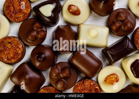 Assortment of delicious chocolate pralines on white table - Stock Photo