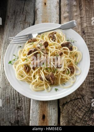Sauteed wiild organic Pied Bleu Mushrooms (Clitocybe nuda) or Blue Foot mushrooms cooked in butter with spaghetti. - Stock Photo