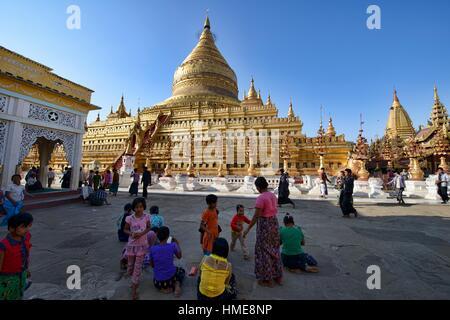 Pilgrims walking at golden Shwezigon Pagoda, Bagan, Myanmar. - Stock Photo