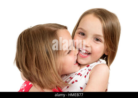 Portrait of cheerful twin sisters hugging , laughing, embracing and smiling at the camera in a studio shoot. Isolated - Stock Photo