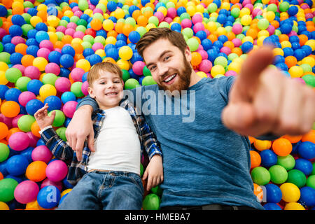 Happy little boy and his father lying and playing at pool with colorful balls - Stock Photo