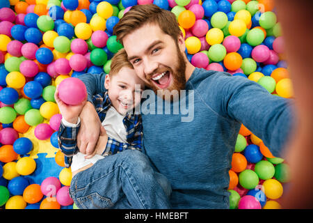 Cheerful bearded dad and little son talking selfie at pool with colorful balls - Stock Photo