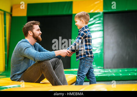Happy bearded father sitting and playing with his little son at indoor amusement park - Stock Photo
