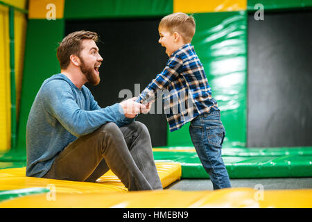Cheerful dad and son having fun and playing together at indoor playground - Stock Photo