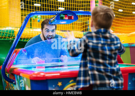 Joyful bearded father and son playing air hockey game at amusement park - Stock Photo