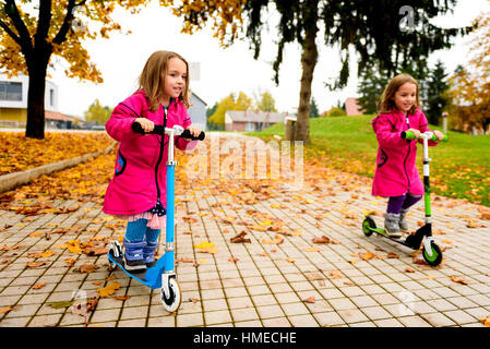 Twin girls in pink coat are riding scooter on maple leaves. Active children in sport pursuit is exercising in the - Stock Photo
