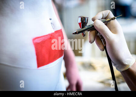Hand holding air brush in body painting woman body. Paintbrush artist is covering body with white and red paint - Stock Photo
