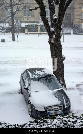 parked car on pavement and snow in town, Strasbourg, Alsace, France. - Stock Photo