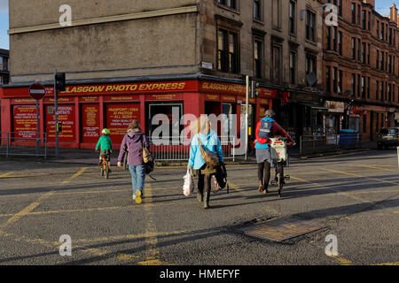 cyclist middle class white people crossing road as a family Govanhill, Glasgow, Scotland, UK - Stock Photo