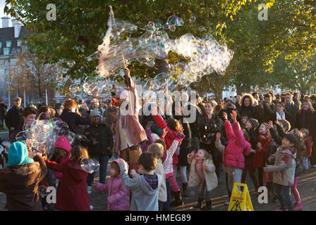 Small children and their parents gather round a street performer leaving a trail of giant bubbles on the South bank - Stock Photo
