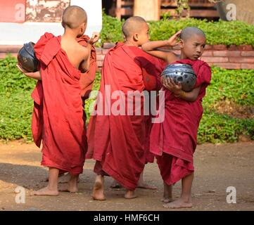 Young monks on their morning alms rounds, Bagan, Myanmar. - Stock Photo