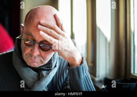 Rotterdam, Netherlands. Balding, middle aged man reading the menu of Hotel New York restaurant, while leaning his - Stock Photo