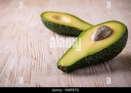 Horizontal photo of single green raw severed avocado which is cut to two halves. Both pieces are placed in a row - Stock Photo