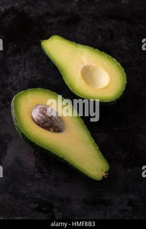Vertical photo of single green raw severed avocado which is cut to two halves. Both pieces are placed in a row and - Stock Photo