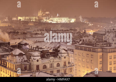 Night winter Prague, the Castle and St. Vitus Cathedral. Snowy roofs of the old town, in the background Prague Castle. - Stock Photo