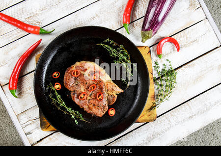 meat with spices in a pan, rosemary, and hot chili peppers on a white wooden table background - Stock Photo
