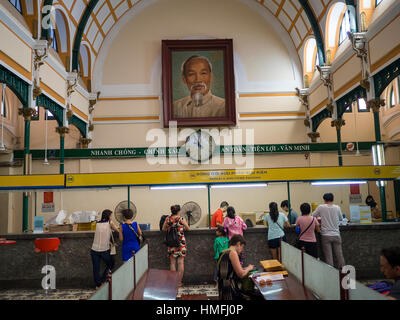 Customers are preparing packages and letters in the french colonial central post office in Saigon, Vietnam - Stock Photo