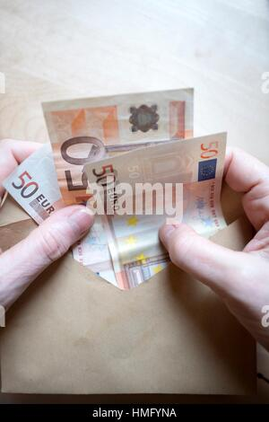 Hands of a woman with fifty euro notes - Stock Photo