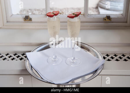 Two glasses of prosecco in champagne flutes with strawberries on a silver tray - Stock Photo