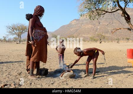 Himba girl starting fire with her mother for the cooking, Marienfluss valley, Kaokoland desert, Namibia. - Stock Photo