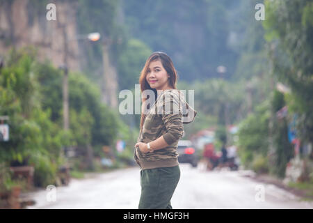 Portrait of beautiful asian young woman near the road - Stock Photo