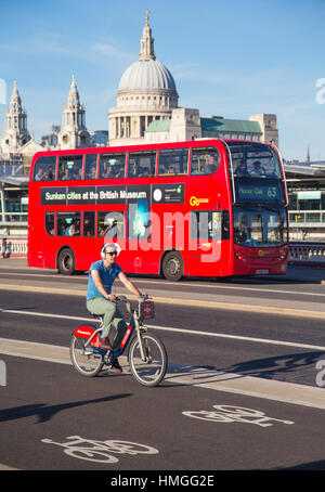 young man riding Santander hire bike on cycle superhighway 6 on Blackfriars bridge, London, with red bus and St - Stock Photo