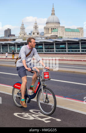 stylish young man riding Santander hire bike in London on north-south cycle superhighway on Blackfriars bridge with - Stock Photo