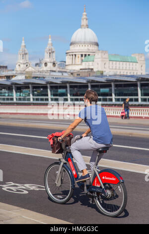 young man riding Santander hire bike on north-south cycle superhighway on Blackfriars bridge, London, with St Pauls - Stock Photo