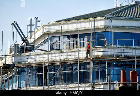 Scaffolder at work wearing regulation health and safety equiptment - Stock Photo