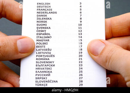 Booklet with list of languages in woman hands. - Stock Photo