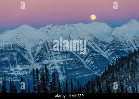 Full moon rising over Canadian Rockies; viewed from Esplanada Range; Selkirk Range; British Columbia; Canada - Stock Photo