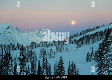 Full moon setting over Canadian Rockies; viewed from Esplanada Range; Selkirk Range; British Columbia; Canada - Stock Photo