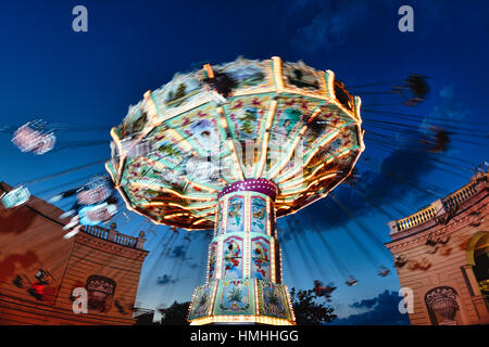 View of a Moving Chain Swing Ride at Dusk, Prater Amusement Park, Vienna, Austria - Stock Photo
