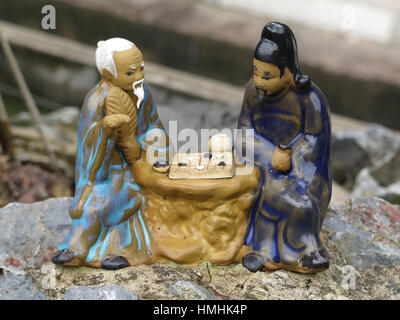 Ceramic ornament of two old Asian men playing chess - Stock Photo