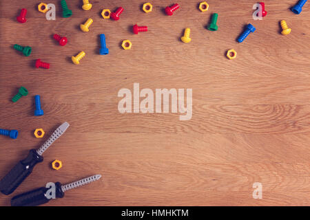 Kids Toys Background Frame Boarder with colorful nuts, bolts and two screwdrivers on wooden table. Top view. Flat - Stock Photo