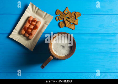 Mug of Beer, Sausage, and Dried Bread on Wooden background - Stock Photo