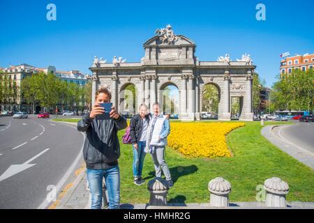 Tourists taking photos at Alcala Gate. Madrid, Spain. - Stock Photo