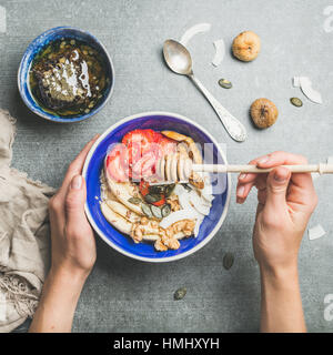 Blue bowl with healthy vegetarian breakfast in woman's hands - Stock Photo
