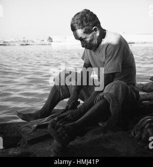 Mann am Rio Manzanares in Cumaná schneidet Fisch auf, Venezuela 1966. Man next to the Rio Manzanares in Cumaná cuts - Stock Photo